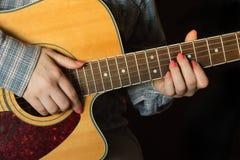 Menina que joga um close up da guitarra acústica Imagem de Stock Royalty Free