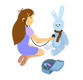 Menina que joga um doutor com o brinquedo do coelho do luxuoso Foto de Stock Royalty Free