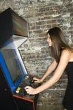 Menina que joga um jogo da arcada Foto de Stock Royalty Free
