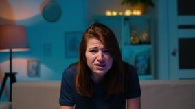 Menina que joga um jogo de vídeo em casa na noite Mulher excitada do gamer que senta-se em um sofá, jogando e perdendo nos jogos  vídeos de arquivo