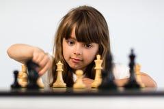 Menina que joga a xadrez Fotos de Stock Royalty Free