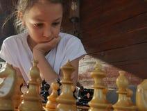 Menina que joga a xadrez foto de stock