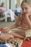 Menina que joga a xadrez com irmão At Porch fotografia de stock