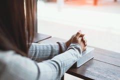 Menina que lê a Bíblia no café Imagens de Stock Royalty Free