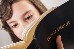 Menina que lê a Bíblia Imagens de Stock