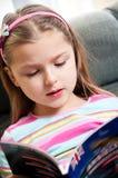 Menina que lê o livro inglês