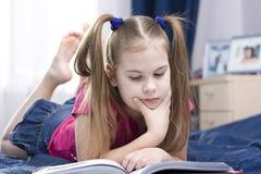 Menina que lê um livro. Fotos de Stock