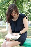 Menina que lê um livro Fotos de Stock Royalty Free