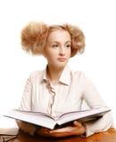 Menina que lê um livro ao sentar-se na tabela imagem de stock royalty free