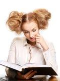 Menina que lê um livro ao sentar-se na tabela fotos de stock royalty free