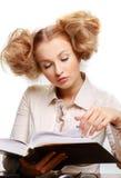 Menina que lê um livro ao sentar-se na tabela imagens de stock