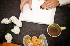 Menina que lê um livro com um copo do chá foto de stock royalty free