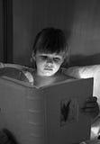 Menina que lê um livro com lâmpada Fotos de Stock
