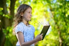 Menina que lê um livro e que voa letras imagens de stock