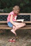 Menina que lê um livro em um banco no parque Foto de Stock