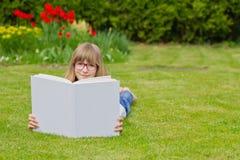 Menina que lê um livro em um jardim Fotos de Stock