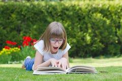 Menina que lê um livro em um jardim Fotos de Stock Royalty Free