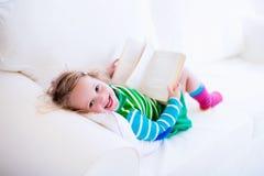 Menina que lê um livro em um sofá branco Fotos de Stock Royalty Free