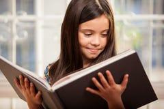Menina que lê um livro grande Fotografia de Stock