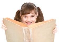 Menina que lê um livro grande Isolado no fundo branco Imagens de Stock Royalty Free
