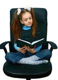 Menina que lê um livro na cadeira fotografia de stock