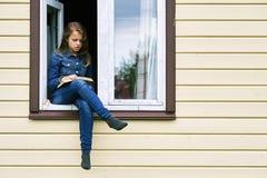 Menina que lê um livro nas férias que sentam-se na janela de uma casa de campo com seus pés que oscilam fora fotografia de stock royalty free