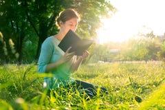 Menina que lê um livro no parque Imagem de Stock Royalty Free