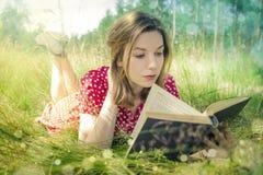 Menina que lê um livro no parque Fotografia de Stock Royalty Free