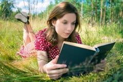 Menina que lê um livro no parque Fotos de Stock
