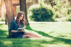 Menina que lê um livro no parque imagens de stock