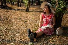 Menina que lê um livro no parque fotografia de stock