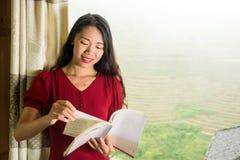 Menina que lê um livro pela janela com uma vista Fotos de Stock Royalty Free
