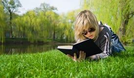 Menina que lê um livro que encontra-se na grama Fotos de Stock