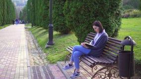 Menina que lê um livro que senta-se em um banco video estoque