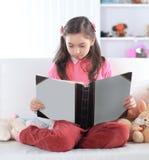 Menina que lê um livro que senta-se no sofá no berçário foto de stock royalty free
