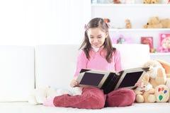 Menina que lê um livro que senta-se no sofá no berçário imagens de stock