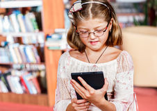 Menina que lê um livro eletrônico Imagem de Stock Royalty Free