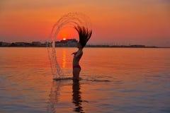Menina que lança a aleta do cabelo na praia do por do sol fotografia de stock
