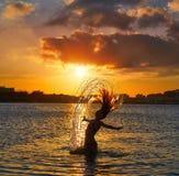 Menina que lança a aleta do cabelo na praia do por do sol fotos de stock