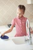 Menina que lava os pratos Fotografia de Stock Royalty Free