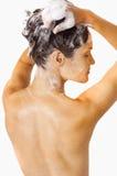 Menina que lava seu cabelo com champô Fotografia de Stock