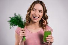 Menina que levanta com suco verde e as hortaliças isolados imagem de stock