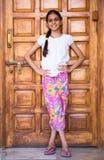 menina que levanta contra uma porta de madeira Fotos de Stock Royalty Free