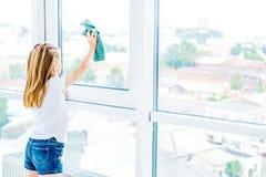 Menina que limpa a superfície da janela imagem de stock