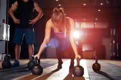A menina que loura bonito fazer empurra levanta no gym Imagens de Stock Royalty Free