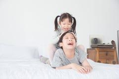 Menina que luta com seu irmão na cama em casa fotos de stock