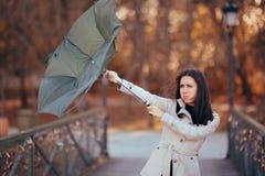 Menina que luta o vento que guarda o guarda-chuva que chove o tempo imagem de stock