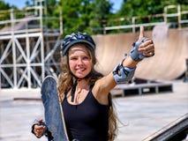 Menina que mantém um skate disponivel Fotografia de Stock Royalty Free