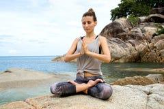 A menina que medita sobre pedras pelo mar, o empréstimo da menina com ioga a ilha Samui, ioga em Tailândia foto de stock royalty free