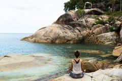 A menina que medita sobre pedras pelo mar, o empréstimo da menina com ioga a ilha Samui, ioga em Tailândia imagem de stock royalty free